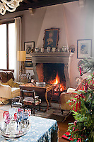 A roaring fire in the living room with an antique games table in front of the fireplace