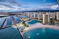 An aerial view at sunset of Ala Wai Harbor, the Hilton Hawaiian Village's lagoon and Kahanamoku Beach, Waikiki, O'ahu.