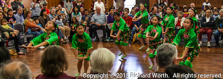 Young dancers from the  China Dance School of San Francisco, dressed in bright green costumes perform in San Leandro, CA to welcome the lunar new year.