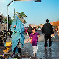 Woman in a burqa and a younger girl walking through Herat.