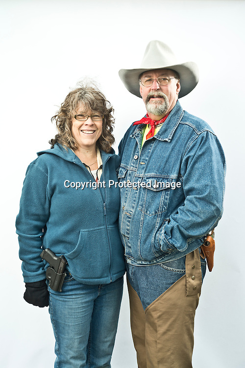 "Carrie Mann and her husband, Craig, of Belfair, were two of about 1,500 gun owners and supporters to attend the Guns Across America rally at the Washington State Capitol in Olympia Saturday, Jan. 19, 2013. Carrie brought her 380 Millenium Taurus .380 ACP Pistol, and Craig brought his .357 S&W Magnum. ""We just support open carry laws and want to support the rights of this state's constitution and our country's constitution,"" said Craig, a member of the Washington state Constitutional Party. Photo by Daniel Berman/www.bermanphotos.com."