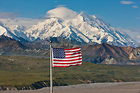 The American flag flies at Eielson Visitor's center with the Summit of Mt McKinley visible in the distance, Denali National Park, interior, Alaska.