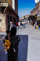 Morocco. Marrakesh medina in the area known as Kasbah. Woman with a child on her arms.