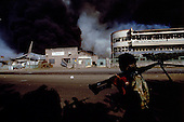 Addis Ababa, Ethiopia<br /> June 4,1991<br /> <br /> An EPRDF fighter patrols an exploding ammunitions depot set alight by former government supporters.<br /> <br /> In late May 1991 the long civil war in Ethiopia came to a climax when the alliance of four rebel groups, the Ethiopian People's Revolutionary Democratic Front (EPRDF), toppled the authoritarian government of Mengistu Haile-Mariam and took control of Addis Ababa and the nation. The governing regime declared a cease-fire and fled. In July 1991 the 24 different groups met in the capital and established a multi-party provisional government headed by Meles Zenawi, the Tigray Rebel Leader, to lead the country to its first free elections within two years.