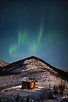 Aurora borealis over the Caribou Bluff recreation cabin in the White Mountains National Recreation Area, interior, Alaska.