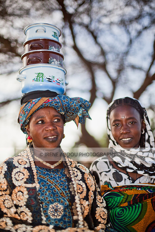 A woman carries a stock of pots on her head through the market of Djibo in northern Burkina Faso.
