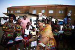SOWETO, SOUTH AFRICA DECEMBER 16: Nondumiso Rakale (c) age 21, dances as she goes through a coming of age ceremony outside her house on December 16, 2006 in Jabulani section of Soweto, Johannesburg, South Africa. She is now seen as a grown woman and she can date men. A cow was slaughtered a day earlier, and all the part of the animal is used in the ceremony. She wears a dried cow skin on her back. Relatives and friends donated money and put it in her hat. Many people fight to keep their old traditions as they are facing difficulties to keep them, because of the life is becoming more westernized. Soweto is South Africa?s largest township and it was founded about one hundred years to make housing available for black people south west of downtown Johannesburg. The estimated population is between 2-3 million. Many key events during the Apartheid struggle unfolded here, and the most known is the student uprisings in June 1976, where thousands of students took to the streets to protest after being forced to study the Afrikaans language at school. Soweto today is a mix of old housing and newly constructed townhouses. A new hungry black middle-class is growing steadily. Many residents work in Johannesburg but the last years many shopping malls have been built, and people are starting to spend their money in Soweto.  .(Photo by Per-Anders Pettersson/Getty Images).