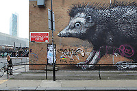 A woman with bicycle stops at the corner of Bethnal Green Road in London, UK to look at a monumental B&W spray paint graffiti of a rat on Huntingdon Estate buidling wall. Picture by Manuel Cohen