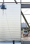 Foto: VidiPhoto<br /> <br /> HETEREN - Aan en op de enorme nieuwe hal in aanbouw van drogisterijketen Kruidvat (A. S. Watson BV) worden donderdag alumium platen en stalen draagbalken aangebracht. De 14.000 vierkante meter grote opslagruimte op bedrijventerrein Poort van Midden Gelderland in Heteren langs de A50, is bedoeld als uitbreiding van het 68.000 vierkante meter grote distributiecentrum, op een steenworp afstand van de nieuwbouw. Het bestaande distributiecentrum (500-800 medewerkers) behoort tot de modernste ter wereld en bevoorraadt dagelijks 1150 winkels van Kruidvat, Trekpleister en Prijsmepper in de Benelux. Op de nieuwe plek worden straks vooral retourzendingen verwerkt. De verwachting is dat de uitbreiding zo'n 40 nieuwe arbeidplaatsen oplevert. Hoofdaannemer is Kuijpers Bouw Heteren. De nieuwbouw moet in de loop van dit jaar in gebruik worden genomen.