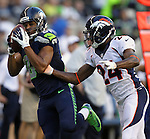 Seattle Seahawks wide receiver Golden Tate catches a 33 yard pass while being defended by is grabbed by Denver Broncos cornerback Champ Bailey at CenturyLink Field in Seattle, Washington on  August 17, 2013. The Seattle Seahawks beat the Broncos 40-10.     ©2013. Jim Bryant Photo. All Rights Reserved.d.