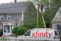 Comcast worker intalls xfinity cable service to residential home, Martha's Vineyard, Massachusetts, USA
