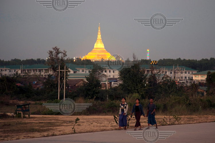 Workers walk past the illuminated replica of the famous Shwedagon Pagoda in Naypyitaw, the new capital of Burma (Myanmar) since November 2005.