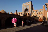 View from the side of a woman with a large pink umbrella walking towards the Allah Kuli Khan Madrasah, 1834-35, Khiva, Uzbekistan, seen in the summer afternoon light on July 7, 2010. The shadowy walkway contrasts strongly with the sunlit tiered arches of the facade in the background. Picture by Manuel Cohen