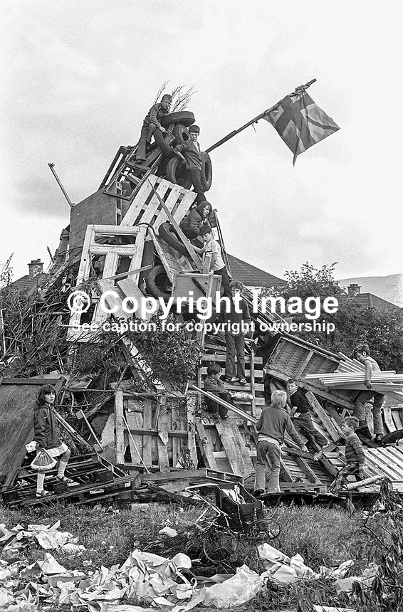 Children building a traditional Eleventh Night bonfire on a Belfast housing estate, N Ireland. The widespread bonfires were a precursor to the Orangemen's Twelfth of July parades the following day. 1974071103871/2, 387/74.<br />