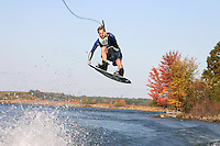 A wakeboarder floats through the air after catching the wake behind a boat in Lake Anna. Boats line the shores of Lake Anna.  water ski boat