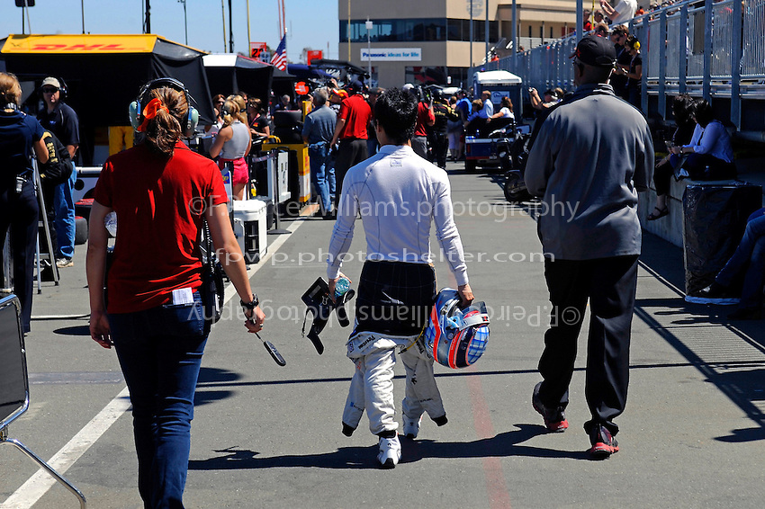 Takuma Sato (#15) walks away from his pit after dropping out of the race on lap 2.