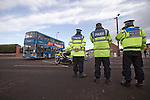 """Portsmouth 1 Southampton 1, 18/12/2012. Fratton Park, Championship. Police officers watcjing a convoy of buses containing Southampton fans approaching Fratton Park stadium down a closed-off street before Portsmouth take on local rivals Southampton in a Championship fixture. Around 3000 away fans were taken directly to the game in a fleet of buses in a police operation known as the """"coach bubble"""" to avoid the possibility of disorder between rival fans. The match ended in a one-all draw watched by a near capacity crowd of 19,879. Photo by Colin McPherson."""