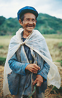 Philippines. Negros Island. Province of Negros Occidental, located in the  Western Visayas region. Barangay (village) Camao. An old smiling man, a farmer, and his hand-made plastic rain coat stands alone in the fields. © 1999 Didier Ruef