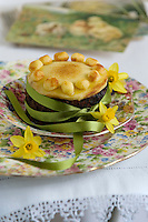 Detail of a simnel cake on a pretty floral plate simply decorated with green ribbon and daffodils