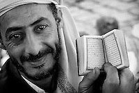 Man at a market in San'a holding a small copy of the Koran.