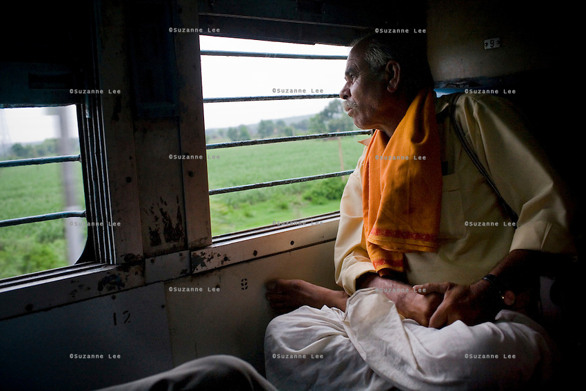 G.G. Goswamy a farmer from Bhopal, looks out at the greenery of Madhya Pradesh state as the Himsagar Express 6318 speeds from Nagpur stn. to Sevagram station on 8th July 2009..6318 / Himsagar Express, India's longest single train journey, spanning 3720 kms, going from the mountains (Hima) to the seas (Sagar), from Jammu and Kashmir state of the Indian Himalayas to Kanyakumari, which is the southern most tip of India...Photo by Suzanne Lee / for The National