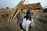 A displaced boy holds his younger sibling in Agok, a town in the contested Abyei region where tens of thousands of people fled in 2011 after an attack by soldiers and militias from the northern Republic of Sudan on most parts of Abyei. Although the 2005 Comprehensive Peace Agreement called for residents of Abyei--which sits on the border between Sudan and South Sudan--to hold a referendum on whether they wanted to align with the north or the newly independent South Sudan, the government in Khartoum and northern-backed Misseriya nomads, excluded from voting as they only live part of the year in Abyei, blocked the vote and attacked the majority Dinka Ngok population. The African Union has proposed a new peace plan, including a referendum to be held in October 2013, but it has been rejected by the Misseriya and Khartoum.
