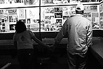 """A couple checks out the """"Wall of Fame"""" featuring photographs, concert flyers and press clippings about bands that have played at Grant's Lounge over the years. Macon, Ga. Nov. 21, 2010."""
