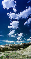 The blue sky is painted with puffs of clouds in the Rocky Mountains west of Denver on the summit of Loveland Pass.  The multiple images have been stiched together in photo editing software to create a single panoramic image.