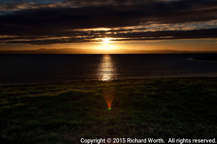A glowing sunset over the bay viewed from the San Francisco Bay Trail in San Leandro and puntuated by a holiday-colored lens flare of red and green.