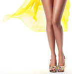 Sexy long legs of a young woman wearing yellow summer beach dress isolated on white background