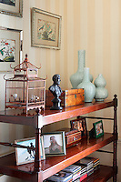 Ceramic vases, wooden boxes and family photohraphs are displayed on a Victorian what not in the corner of a room.
