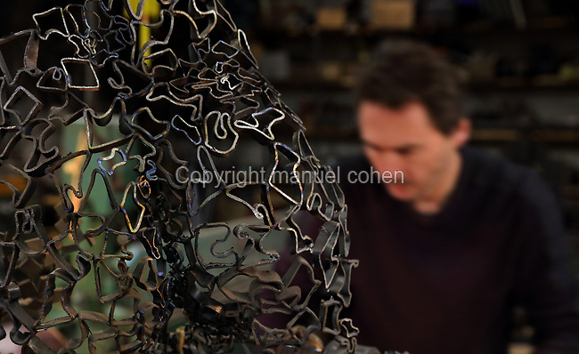 Nicolas Desbons, metalworker and artist, and a sculpture made from cross-sections of steel tubes manipulated into organic profiles and soldered together, in his Soleil Rouge workshop, photographed in 2017, in Montreuil, a suburb of Paris, France. Desbons works mainly in steel but often in conjunction with other materials such as fibreglass, glass and clay, using both cold metal and forge techniques. He produces both figurative and abstract sculptures as well as furniture and lighting. Picture by Manuel Cohen