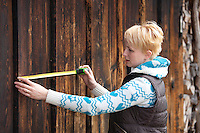 Close-up of young caucasian woman measuring old wooden wall  using tape measure