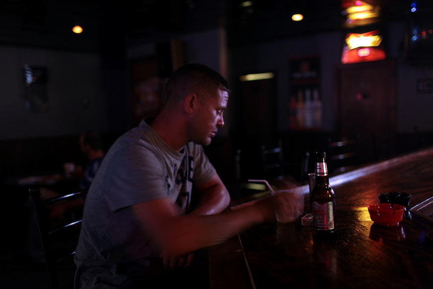 Jason Melerine sits alone at a bar in St Bernard, LA on August 24th. Working for BP since the oil spill closed the fishing community down, Jason was depressed, worried about his family and the future of fishing in the small rural community.