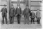 COURTHOUSE DENIZENS, C. 1915. The north steps of the post office are the setting for this group portrait, which includes a policeman and two newsboys. Mirrored in the glass doors is a sign for Deluxe Studio, a photographer's establishment north across P Street from the courthouse. John Johnson's care in composing images suggests he was probably aware of this reflection.<br /> <br /> Photographs taken on black and white glass negatives by African American photographer(s) John Johnson and Earl McWilliams from 1910 to 1925 in Lincoln, Nebraska. Douglas Keister has 280 5x7 glass negatives taken by these photographers. Larger scans available on request.