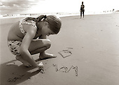 A little girl on the beach professes her undying love for her mother.