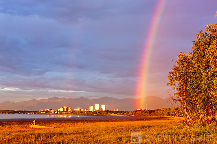 Rainbow over the Anchorage skyline, sunset light reflecting off the buildings, Knik Arm coastal mudflats in the foreground Chugach mountains in the background, Anchorage, Southcentral Alaska, Summer. HDR Image
