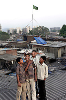 Standing on the roofs of slum houses with a view across Dharavi, a boy laughs with friends as a pigeon sits on his head.