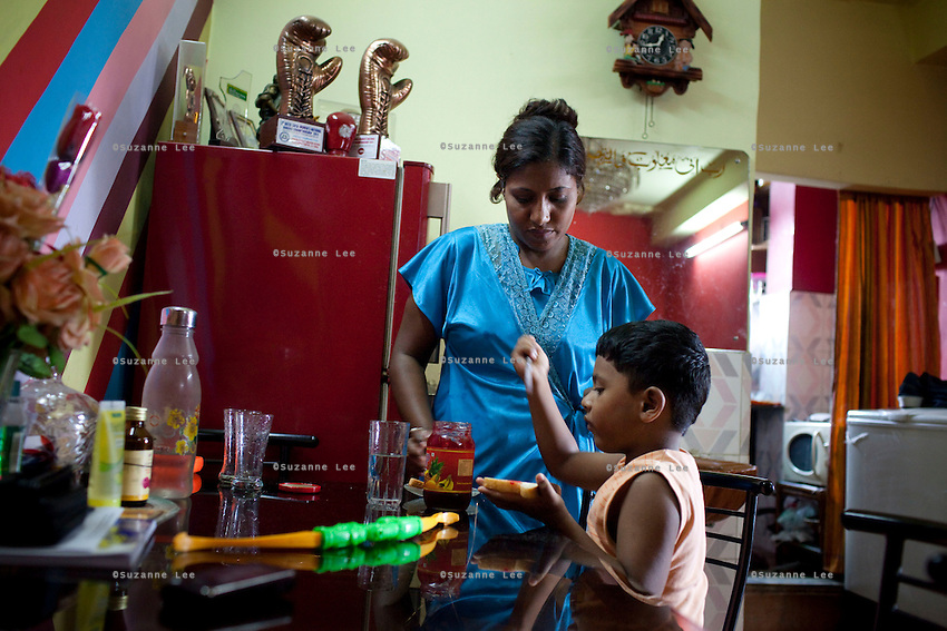 Razia Shabnam (in blue) helps her son with lunch at home in Ekbalpore, Calcutta, West Bengal, India. Razia Shabnam, 28, was one of the first women boxers in Kolkata. She was also the first woman in her community to go to college. She is now a coach and one of only three international female boxing referees in India.  Photo by Suzanne Lee for Panos London