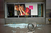 New York, New York.October 30, 2012..An employee of this T-Mobile store in lower Manhattan phones the authorities as she surveys damage caused by looters during the storm.