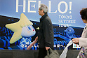 May 22, 2011, Tokyo, Japan - Visiter passes in front of the advertisement of the Tokyo Skytree Town . Tokyo Skytree, the world's tallest self-standing telecommunications tower with a height of 634 meters, opens today. This new Japanese landmark is expected to attract approximately 200,000 visitors on this first official opening day to the general public. (Photo by Yumeto Yamazaki/Nippon News)
