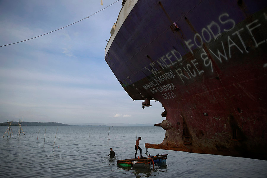 Divers take a part in an effort to recover a ship brought inland by Typhoon Haiyan in Tacloban January 15, 2015. On his first visit to Asia's largest Catholic nation, Pope Francis will visit the central province of Leyte, which is still struggling to recover from Typhoon Haiyan that killed 6,300 people in 2013. About two million people are expected to attend an open-air mass on Saturday at Tacloban City airport, almost completely destroyed by Haiyan. REUTERS/Damir Sagolj (PHILIPPINES)