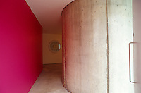 The entrance to the property is heralded by a bright red wall and the massive curved concrete support for the building