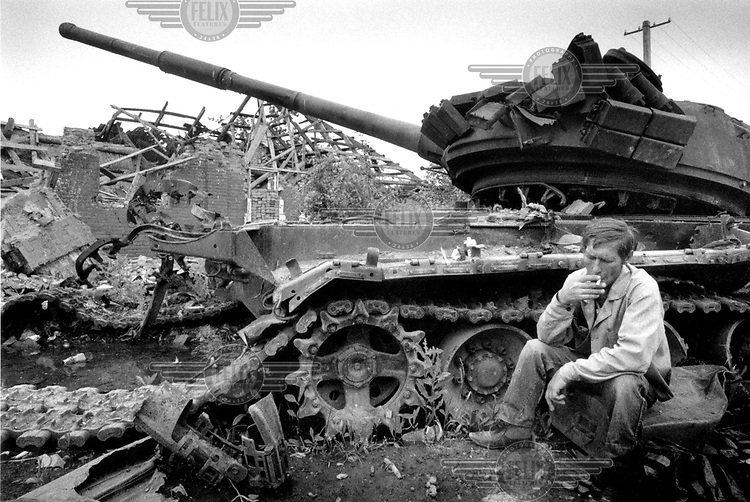"""©Heidi Bradner/Panos Pictures..Chechnya. Vika, A Russian man who was born in Grozny, sits near a destroyed tank in central Grozny """"to remember the crew that died inside,"""" he said. The number of ethnic Russians in Grozny has dramatically decreased since the start of the first war."""