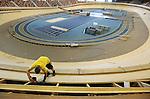 Foto: VidiPhoto<br /> <br /> APELDOORN - Personeel van wielerbaanspecialist SDA Velodromes uit Stompetoren, werkt dinsdag aan de laatste 'ronde' van de nieuwe wielerpiste van Omnisport in Apeldoorn. Het internationale wielersportcomplex wordt op dit moment voorzien van een compleet nieuwe wielerbaan van accoyahout, de tweede in Nederland. Het hout wordt ge&iuml;mporteerd uit Nieuw-Zeeland en krijgt in Nederland een behandeling waardoor het nog harder wordt en niet meer werkt. Zo'n hardhouten wielerbaan zorgt naar verwachting onmiskenbaar voor nieuwe wereldrecords. De oude piste van larixhout moest vervangen worden omdat de luchtvochtigheid in de hal te sterk wisselde en het hout teveel kromp. Daardoor werd Omnisport afgekeurd door de internationale wielerunie UCI voor het houden van internationale wielerwedstrijden. Accoya wordt veelal gebruikt voor kozijnen en is flink duurder dan larix. De gemeente Apeldoorn investeert in de totale vernieuwing 960.000 euro. De baan wordt in juli officieel opgeleverd, zodat de eerste wielerwedstrijden in september gereden kunnen worden.