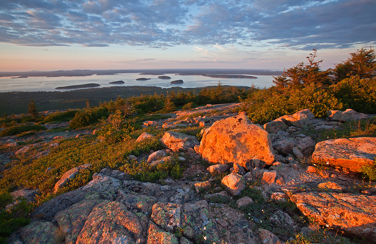 Granite rocks atop Cadillac Mountain with view of the Porcupine Islands and Bar Harbor, Acadia National Park, Maine, USA
