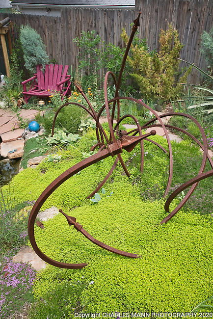 In his Denver garden, Dan Johnson recycled some curved angle iron and finials to create this curvy art object.