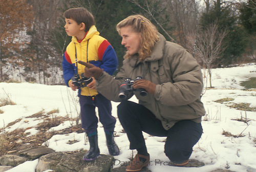 Mother and son watching birds on snowy day in midwest