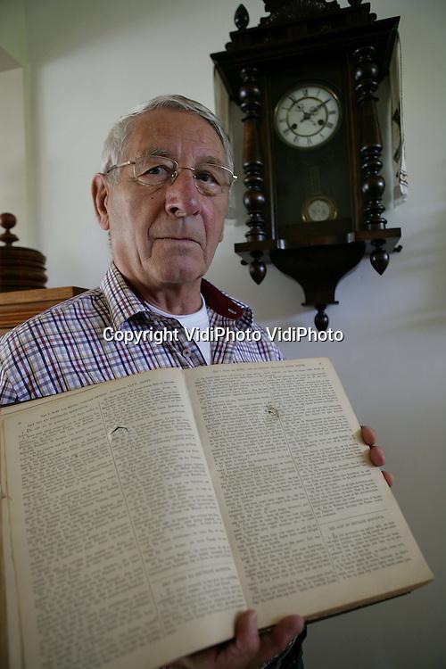 Foto: VidiPhoto..HEELSUM - De heer Loos met de twee enige voorwerpen die de Slag om Arnhem in zijn ouderlijk huis overleefden: de klok en de Statenbijbel (met kogelgaten).
