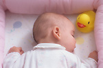 Baby sleeping peacefully in crib with plastic yellow duck